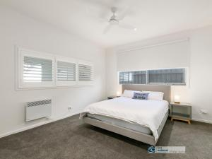 A bed or beds in a room at Pukeko Beach House, Rhyll