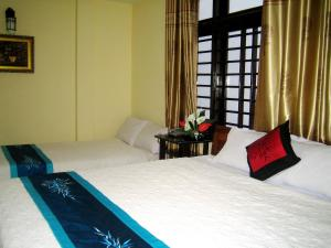 A bed or beds in a room at Champa Hue Hotel