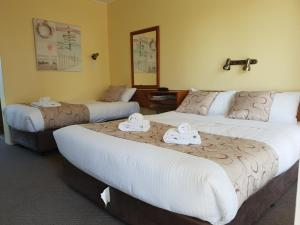A bed or beds in a room at Moon River Motor Inn