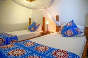 A bed or beds in a room at Indigo Beach Zanzibar
