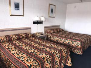 A bed or beds in a room at Super Lodge Motel El Paso