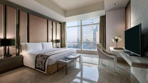 A bed or beds in a room at The Residences of The Ritz-Carlton Jakarta Pacific Place