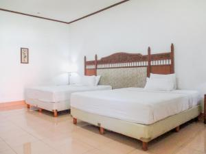 A bed or beds in a room at Inna Bali Heritage Hotel