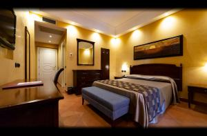 A bed or beds in a room at Artemis Hotel
