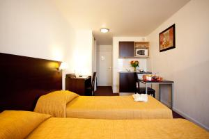 A bed or beds in a room at Aparthotel Adagio Access Paris Saint-Denis Pleyel