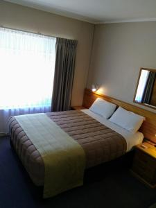 A bed or beds in a room at Armidale Rose Villa Motel