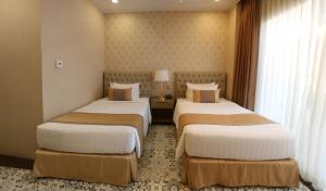 A bed or beds in a room at Rizal Park Hotel