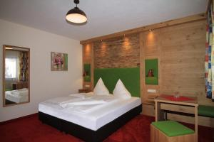 A bed or beds in a room at Hotel Garni Pradella