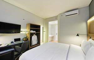 Cama ou camas em um quarto em Hampton by Hilton Guarulhos Airport