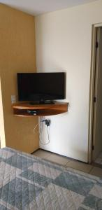 A television and/or entertainment centre at ApartHotel - Praia Mansa 1 e 2 Qtos