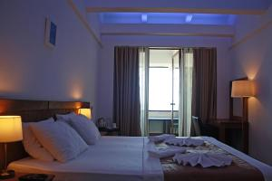 A bed or beds in a room at DEM Hotel