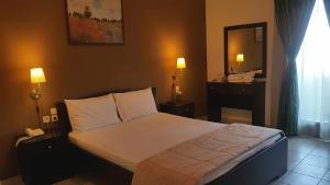 Ένα ή περισσότερα κρεβάτια σε δωμάτιο στο Ξενοδοχείο Οδυσσέας