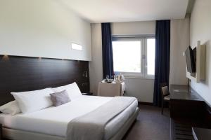 A bed or beds in a room at iH Hotels Pomezia Selene