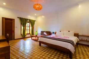 A bed or beds in a room at Le Jardin d'Angkor Hotel & Resort