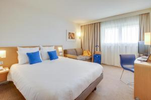 A bed or beds in a room at Novotel Poissy Orgeval