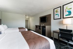 A bed or beds in a room at Quality Inn & Suites