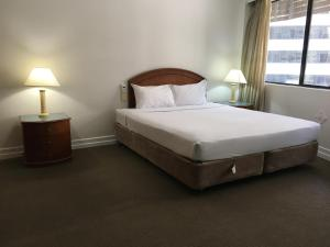 A bed or beds in a room at Great Southern Hotel Brisbane