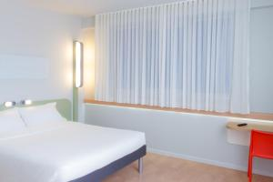 A bed or beds in a room at Ibis Budget Braga Centro