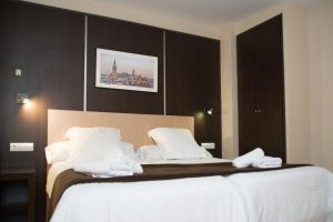 A bed or beds in a room at Hotel Plaza