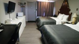 A bed or beds in a room at Port Motel