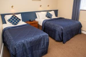 A bed or beds in a room at Leens Hotel