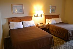 A bed or beds in a room at The Miramar Inn & Suites