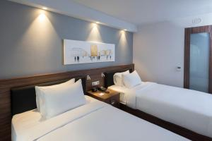 A bed or beds in a room at Hampton By Hilton Poznan Old Town