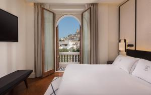 A bed or beds in a room at Gran Hotel Montesol Ibiza