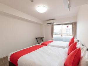 A bed or beds in a room at Guest House One More Heart Enmachi