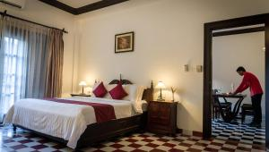 A bed or beds in a room at Chateau d'Angkor La Residence