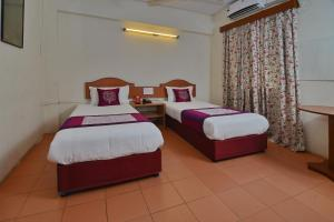 A bed or beds in a room at OYO 2195 Hotel Maharaja