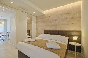 A bed or beds in a room at The Rooms Apartments Tirana