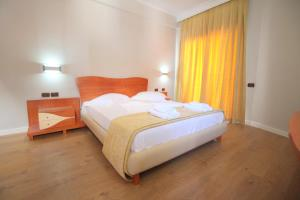 A bed or beds in a room at Hotel Saranda International