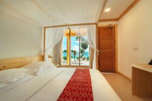 A bed or beds in a room at WAVE SOUND by 3S Maldives