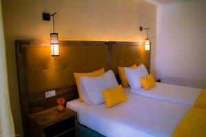 A bed or beds in a room at Hotel Adrar Agadir