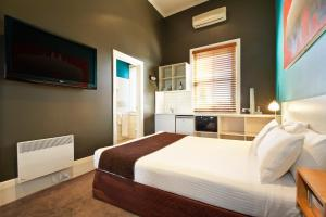 A bed or beds in a room at Tolarno Hotel