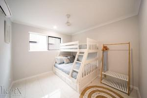 A bunk bed or bunk beds in a room at Airlie on Main Street - Central Airlie Beach Apartment with Ocean Views