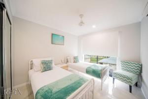A bed or beds in a room at Airlie on Main Street - Central Airlie Beach Apartment with Ocean Views