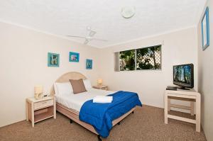 A bed or beds in a room at Champelli Palms Apartments