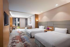 A bed or beds in a room at Ramada by Wyndham Beijing Airport