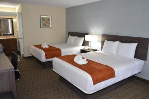 Cama ou camas em um quarto em Days Inn & Suites by Wyndham Orlando Airport