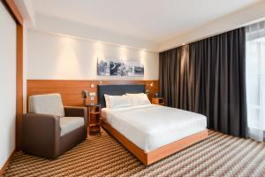 A bed or beds in a room at Hampton by Hilton Warsaw Airport