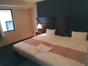 A bed or beds in a room at Hotel Sunline Fukuoka Hakata Ekimae