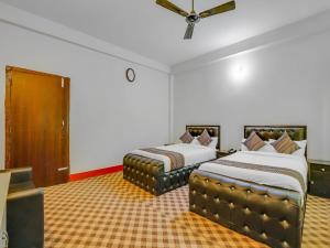 A bed or beds in a room at Hotel Dravya Kuteer
