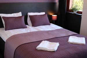 A bed or beds in a room at Nacka Stadshotell