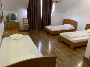 A bed or beds in a room at Pensiunea Man President