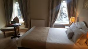 A bed or beds in a room at Mercantile Hotel