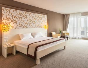 A bed or beds in a room at Continental Hotel