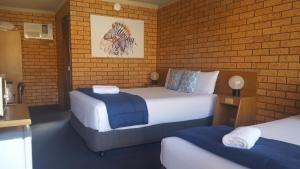 A bed or beds in a room at Royal Palms Motor Inn