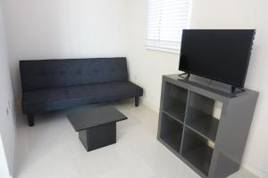 A television and/or entertainment center at Room with ensuite and private kitchen Higher Heights, Barbados